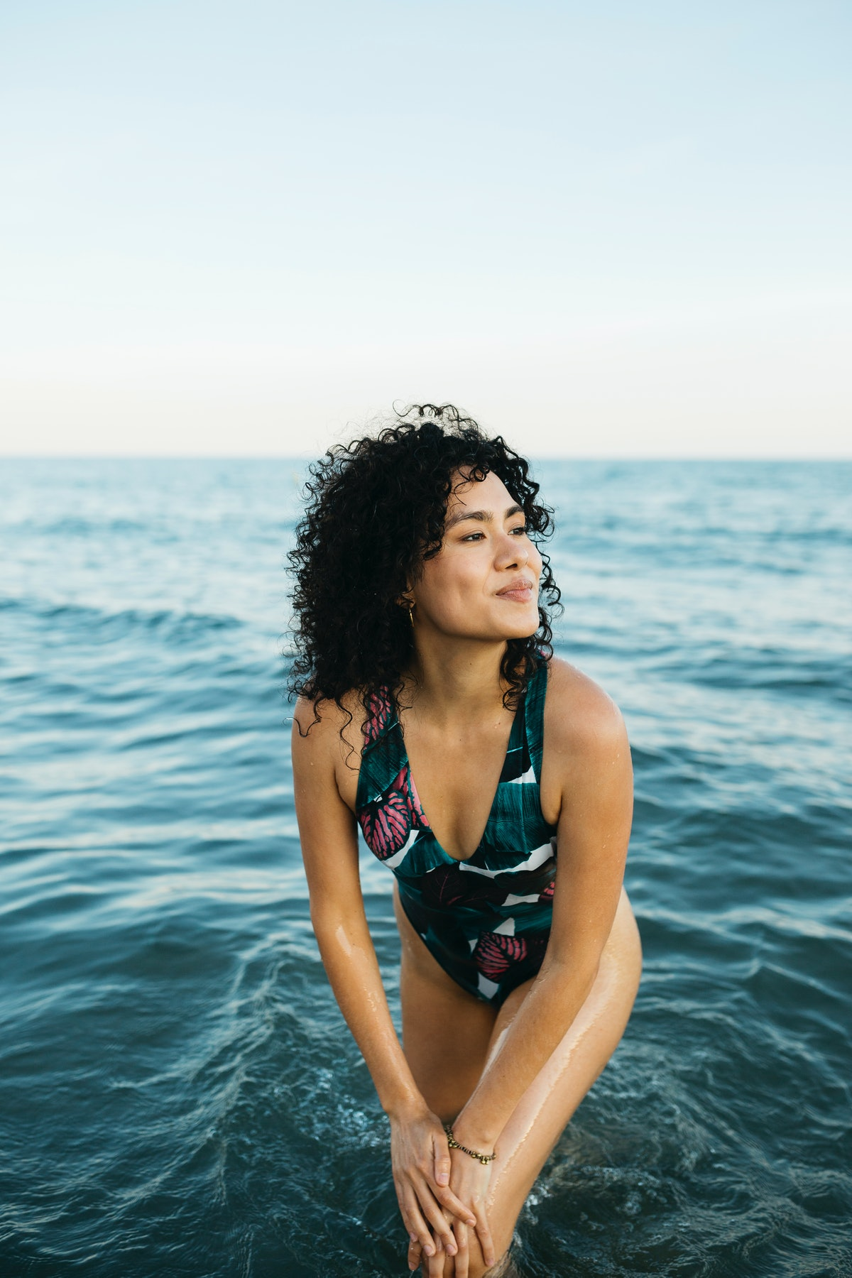 Young woman wearing swimsuit in the sea, smiling while the July 2021 new moon affects her the most.
