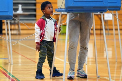 Karter Benson, 4, watches his mom Ceara Hinton vote at the North High School gymnasium polling locat...