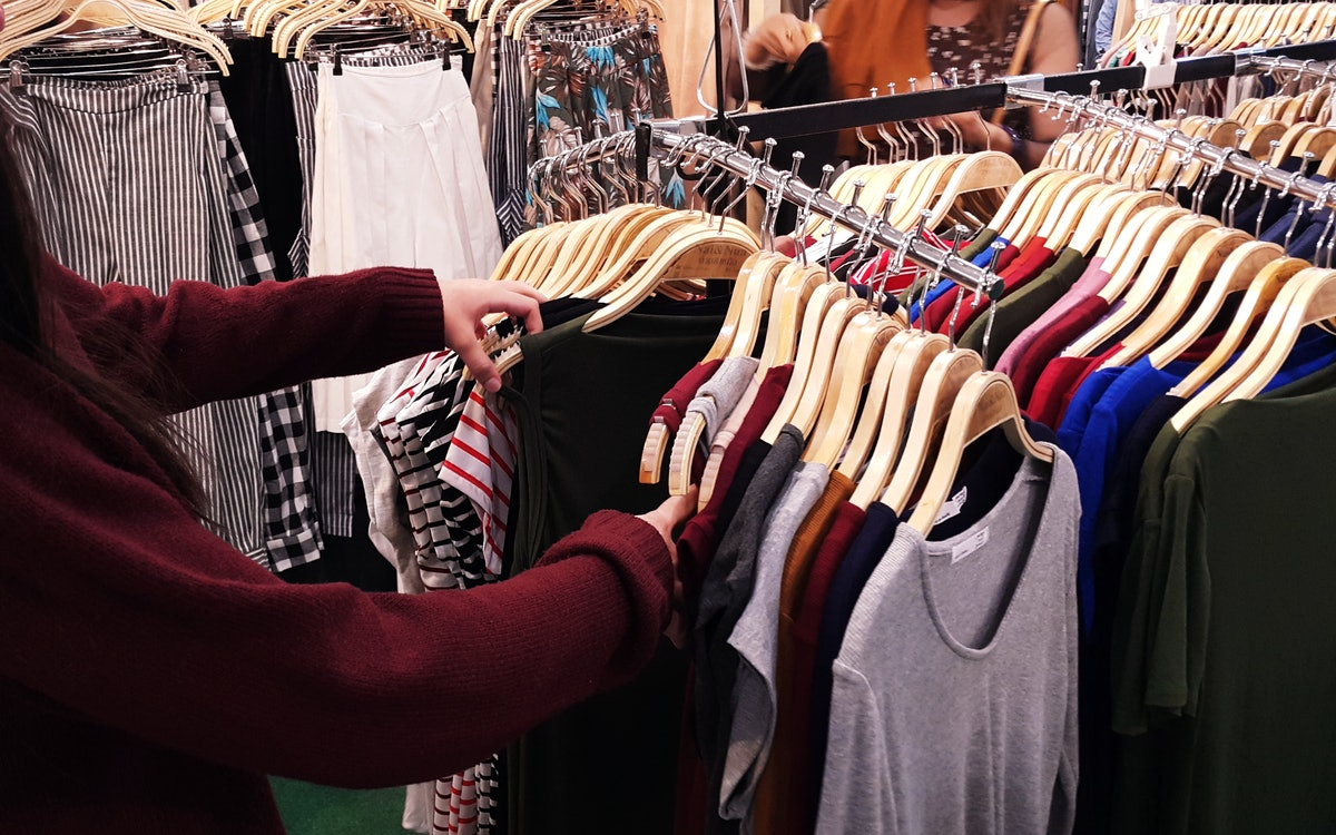 A person looking through clothing racks at a store