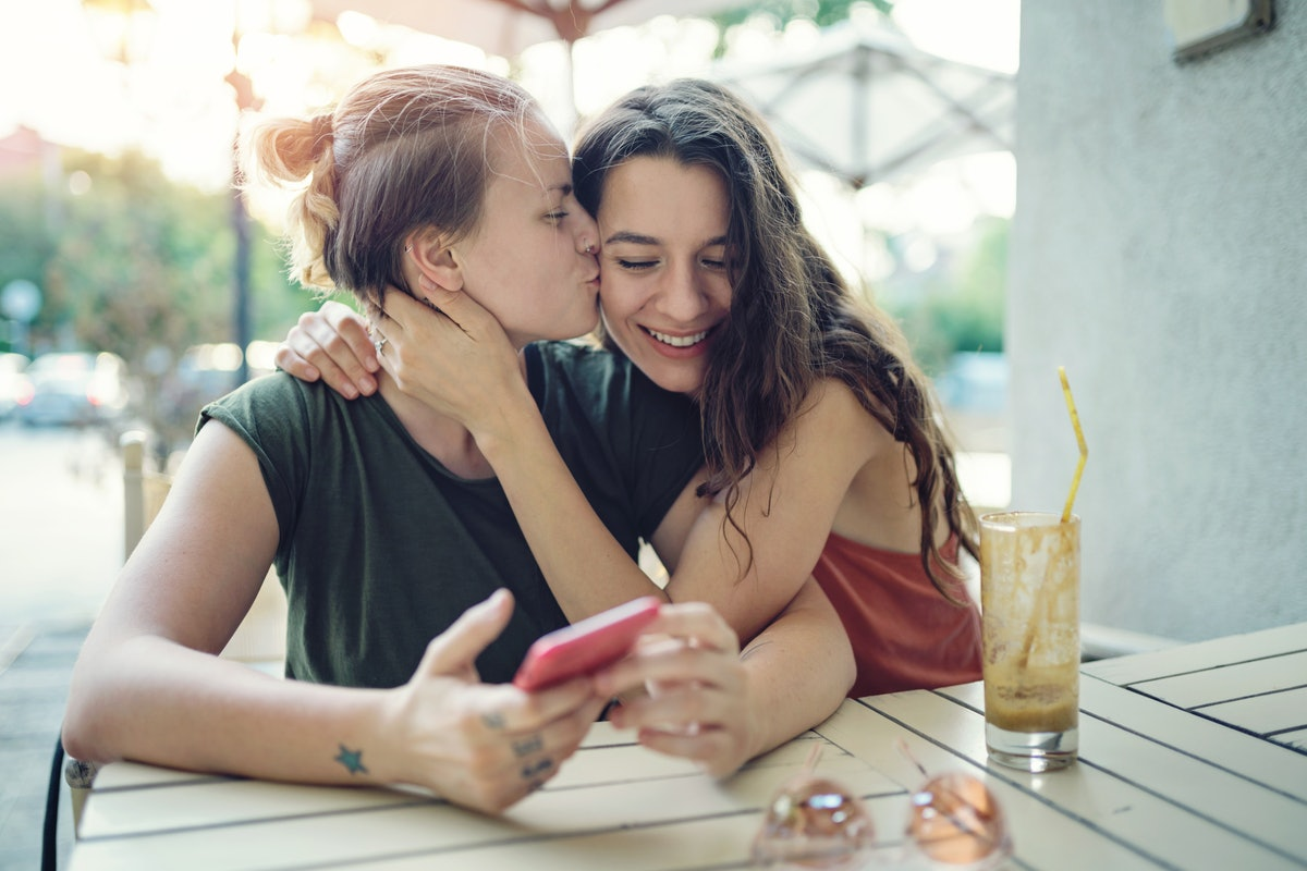 Young happy women drinking ice coffee outdoors on a hot summer day, embracing, kissing and having fun