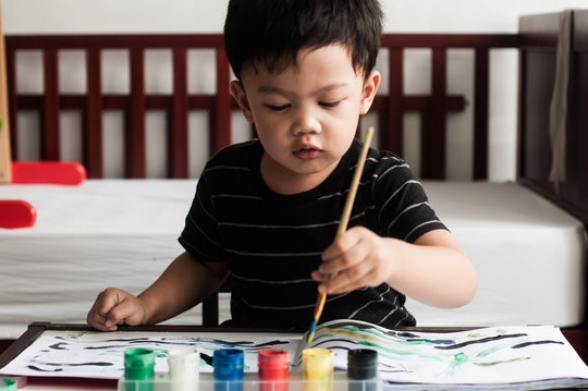 A front view candid portrait of Southeast Asian male toddler painting at home