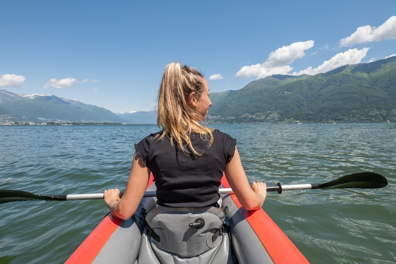 View of a young woman canoeing on beautiful mountain lake in Switzerland.  Inflatable red canoe on water with mountain scenery People travel outdoor activity concept