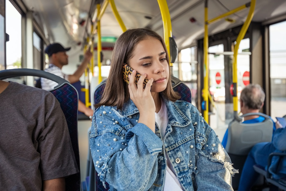 Teenage girls talking on mobile phone in bus. Female passenger is traveling in public transport. She is wearing casuals.