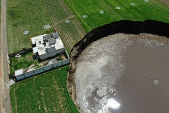 Aerial view of a sinkhole that was found by farmers in a field of crops in Santa Maria Zacatepec, state of Puebla, Mexico on June 01, 2021. (Photo by JOSE CASTAÑARES / AFP) (Photo by JOSE CASTANARES/AFP via Getty Images)