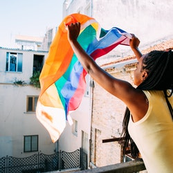 A woman waves a Pride flag out her window. Finding the best LGBT charities to donate to is a great way to celebrate Pride month.