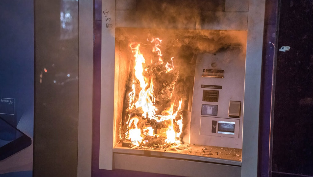 BARCELONA, CATALONIA, SPAIN - 2021/02/20: An ATM seen on fire during the demonstration. Protesters demonstrated for the Fifth day after rapper Pablo Hasél was detained for insulting the Spanish Royal Family in his songs and other alleged acts of violence. (Photo by Thiago Prudencio/SOPA Images/LightRocket via Getty Images)
