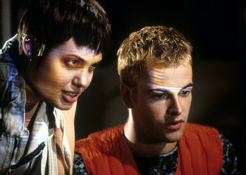 Angelina Jolie stands behind Jonny Lee Miller in a scene from the film 'Hackers', 1995. (Photo by United Artists/Getty Images)