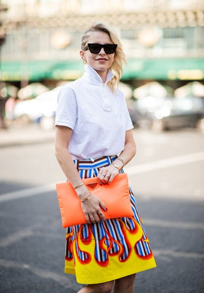 PARIS, FRANCE - JULY 02: Caroline Daur wearing orange Prada bag, white polo shirt, skirt with fire print, Prada heels is seen outside Schiaparelli on day two during Paris Fashion Week Haute Couture FW18 on July 2, 2018 in Paris, France. (Photo by Christian Vierig/Getty Images)