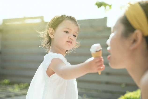 A toddler wearing a white dress offers an ice cream cone to her mother in a sunny spring day in the ...
