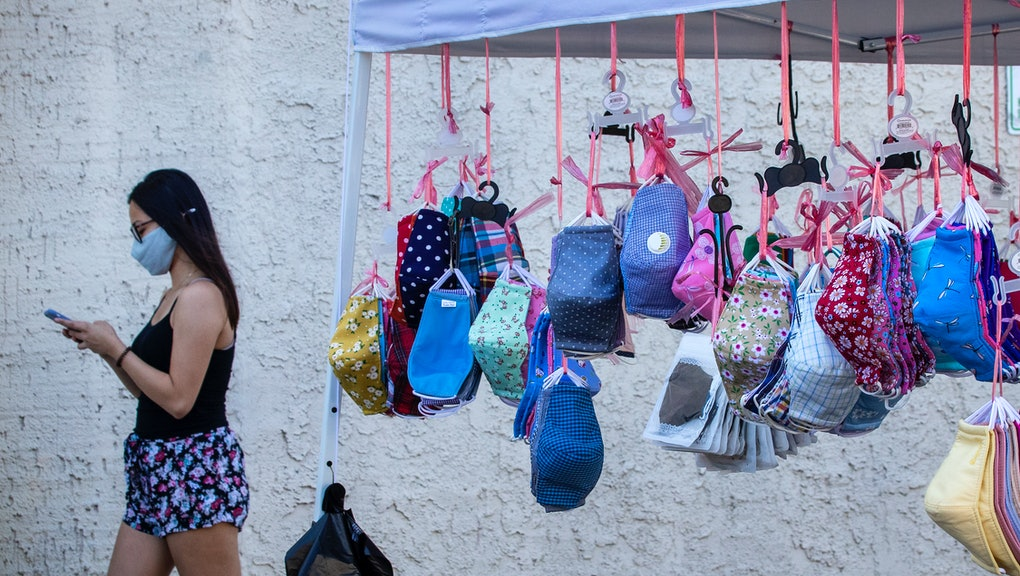 WESTMINSTER, CA - AUGUST 05:  Protective masks hang from a tent as a shopper passes by wearing a mas...