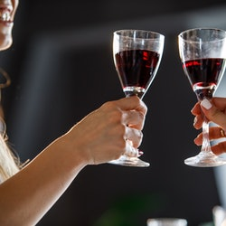 Close up shot of two unrecognizable women cheering to friendship and good health with glasses of red...
