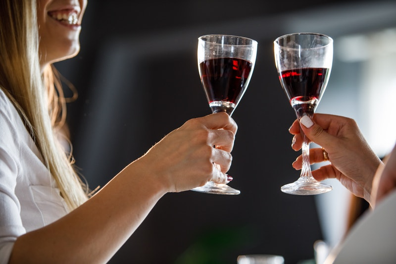 Close up shot of two unrecognizable women cheering to friendship and good health with glasses of red wine.