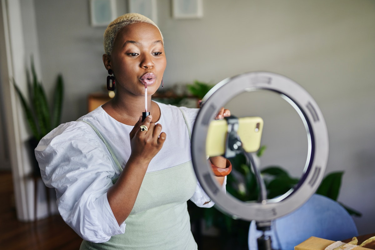 Young African female influencer showing how to apply lip gloss while doing a vlog post from home usi...