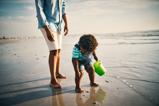 Photo of a young man spending time at the beach with his adorable daughter