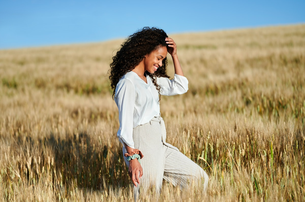 A person smiles as they walk through a field. Walking meditations are about slowing down your thoughts.