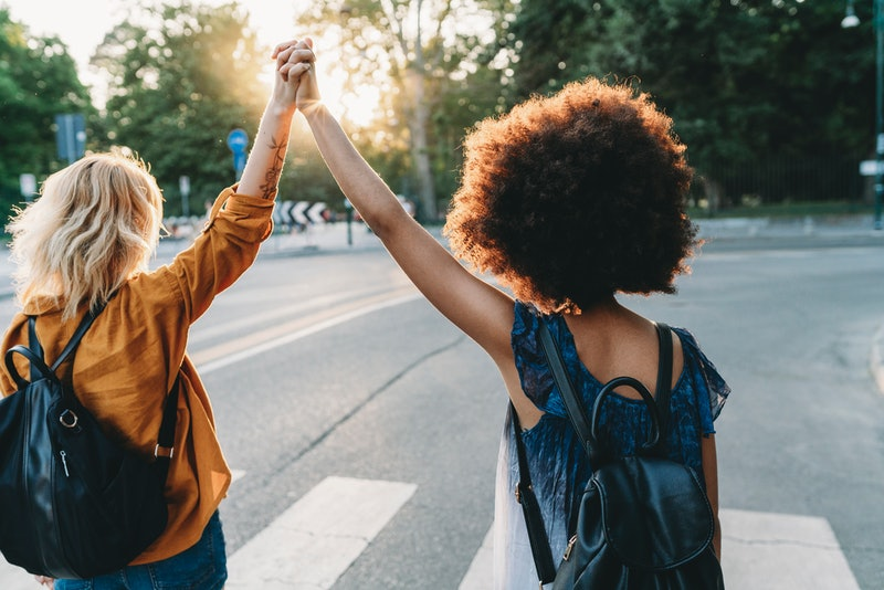 Two friends walking together in the city at sunset pivot away from a hug. Post-pandemic friendship a...