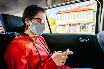 A woman looks at her phone wearing a mask, about to have a panic attack. Why do i sweat when i'm col...