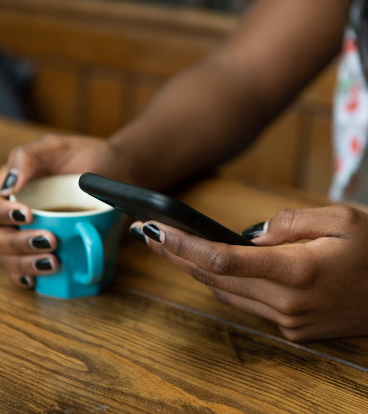 Young woman sitting at a wooden kitchen table, texting on her phone