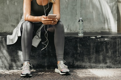 Woman takes a moment to check social media on her smartphone during a running session.