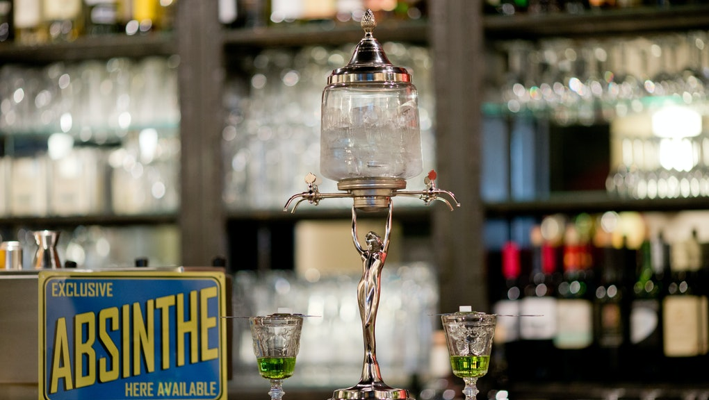 An absinthe fountain seen on the counter at the bar of the 'Casablanca' cinema in Nuremberg, Germany, 19 May 2016. Perforated metal spoons with hooks are designed to fit on absinthe glasses so that the sugar cubes, that are placed on top of the spoon, get dissolved by dripping ice water from the absinthe fountain. Tujon-containing absinthe was banned in Germany and most of Europe for decades. Today, the spirit drink, made from the wormwood plant, has become an iconic cult drink. Photo:DANIEL KARMANN/dpa | usage worldwide   (Photo by Daniel Karmann/picture alliance via Getty Images)