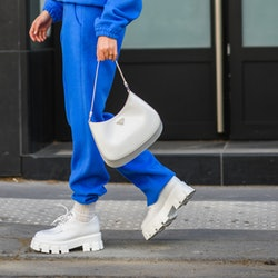 PARIS, FRANCE - APRIL 23: Xenia Adonts wears a pearls necklace, a royal blue V-neck sweater with matching large Shabderb jogger sport pants, a gold watch, a gold ring, a white shiny leather Prada handbag, white shiny leather platform sole Prada loafer shoes, on April 23, 2021 in Paris, France. (Photo by Edward Berthelot/Getty Images)