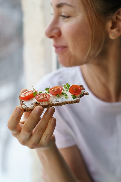 A woman eats an open faced sandwich to avoid low blood sugar, a common reason for sweating when cold