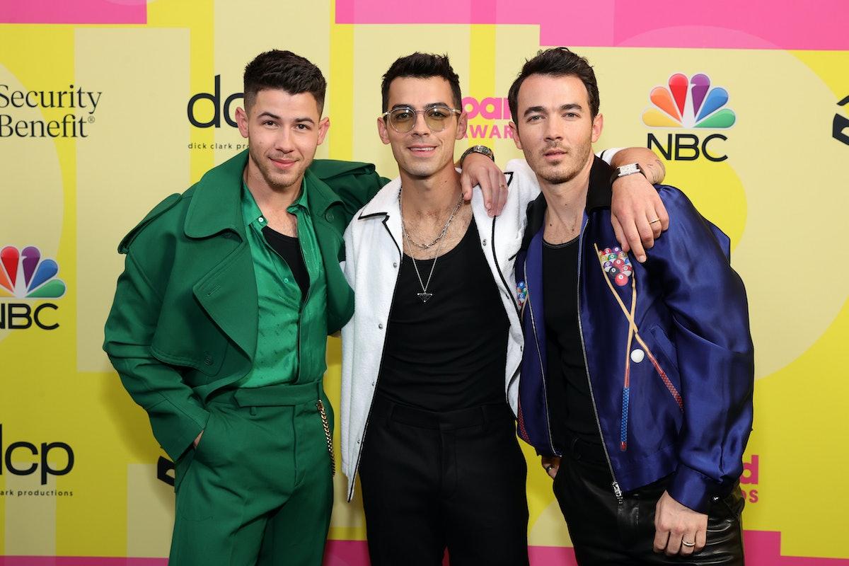 Nick Jonas, Joe Jonas, and Kevin Jonas of Jonas Brothers pose backstage at the 2021 Billboard Music Awards.