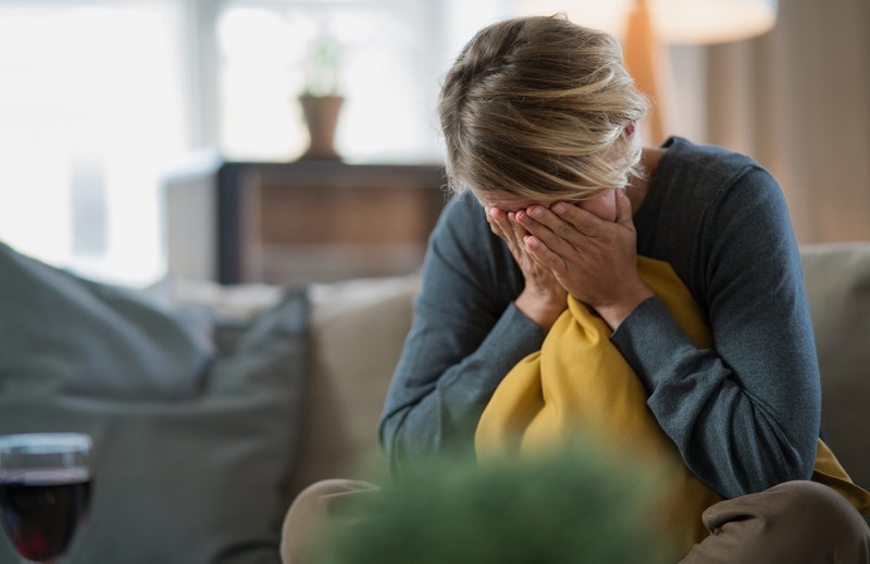 Sad and stressed woman indoors on sofa at home crying, mental health and coronavirus concept.