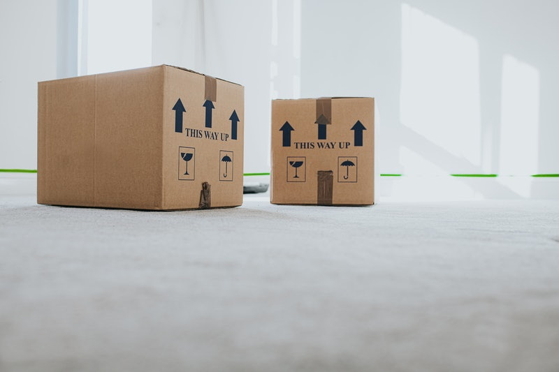 Conceptual image of cardboard boxes stacked in a neutral empty sunny room. Space for copy.