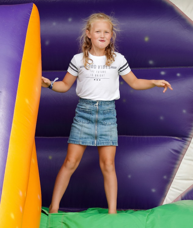 Queen Elizabeth's eldest great grandchild, Savannah Phillips, plays on an inflatable bouncy slide at The Festival of British Eventing on August 3, 2018 in Stroud, England.