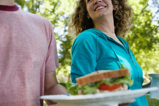 a man holds a platter with a sandwich on it next to a pregnant woman