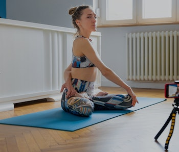 Woman recording yoga class tutorial, sitting in lotus pose on exercise mat at home with left arm beh...