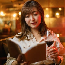 A woman is enjoying reading a book and drinking red wine in a cozy comfortable  cafe & bar at night.
