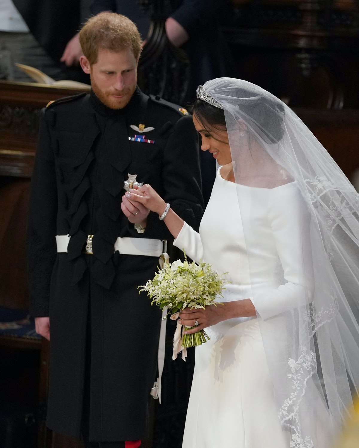 Meghan Markle, Duchess of Sussex, walk back down the aisle away with a bouquet of lillies.