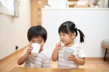 Asian children, brother and sister, drinking cup of milk in the room