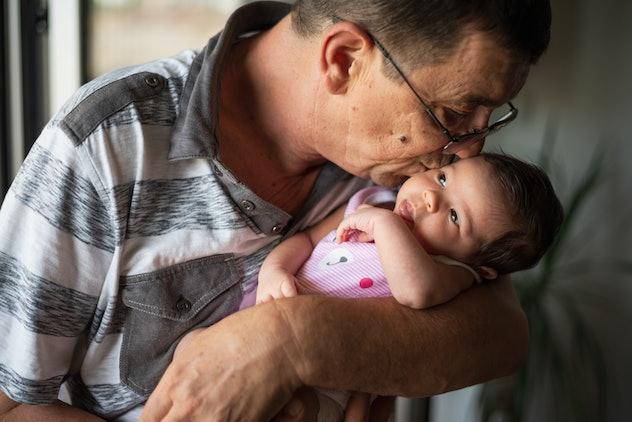 Grandfather embracing newborn baby.