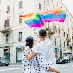 A couple waves a rainbow flag in a city. Here's what the rainbow represents on the gay pride flag.