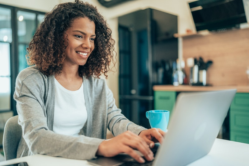 Beautiful afro-american woman using laptop at home