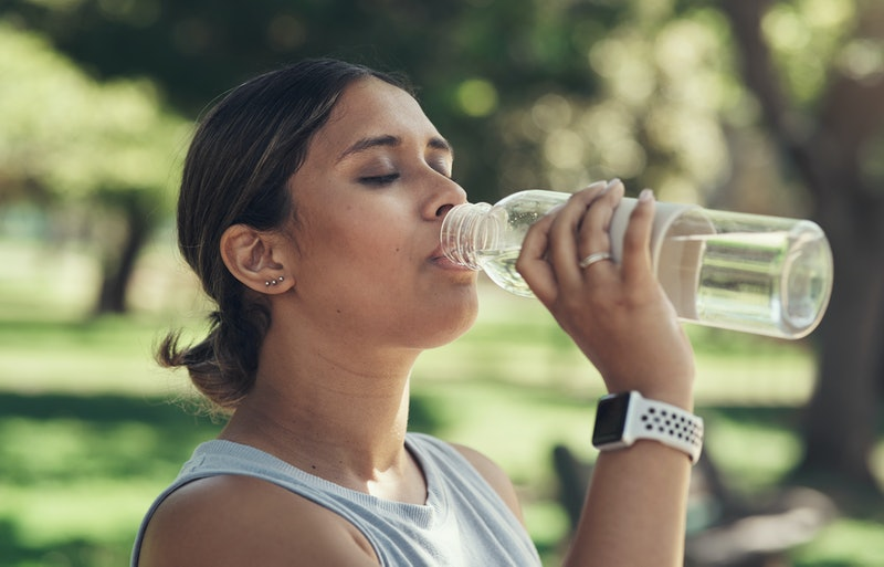 A person closes their eyes while drinking from a water bottle outside. Dry scooping pre-workout won't make it more effective, but it will make it more dangerous.