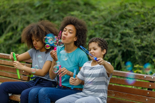 Mother of African-American Ethnicity is Sitting with Son and Daughter on a Bench in Public Park and ...