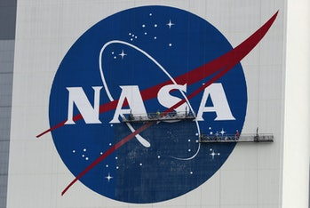CAPE CANAVERAL, FLORIDA - MAY 28: Workers repaint the NASA logo on the Vehicle Assembly Building at the Kennedy Space Center on May 28, 2020 in Cape Canaveral, Florida. SpaceX's Crew Dragon spacecraft will try to launch again on Saturday after weather scrubbed yesterday's attempt. It will be the first manned mission since the end of the Space Shuttle program in 2011 to be launched into space from the United States. (Photo by Joe Raedle/Getty Images)