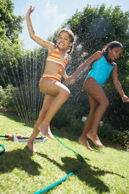 Photo of two children running through a sprinkler on a sunny day.