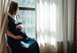 pregnant woman sitting by window looking outside