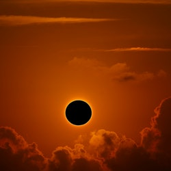 A solar eclipse against clouds. Is it safe to go outside during an eclipse?
