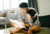 dad and daughter reading a book together