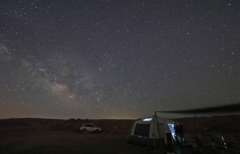 TOPSHOT - The Milky Way illuminates the sky over a campsite in Makhtesh Ramon (Ramon crater) near Israel's Negev desert town of Mitzpe Ramon, on June 7, 2021. - Ramon Crater is a geological feature of Israel's Negev desert during which the crater was formed by erosion and not by impact from a meteor nor by volcanic activity, making ot the world's largest erosion crater. (Photo by Emmanuel DUNAND / AFP) (Photo by EMMANUEL DUNAND/AFP via Getty Images)