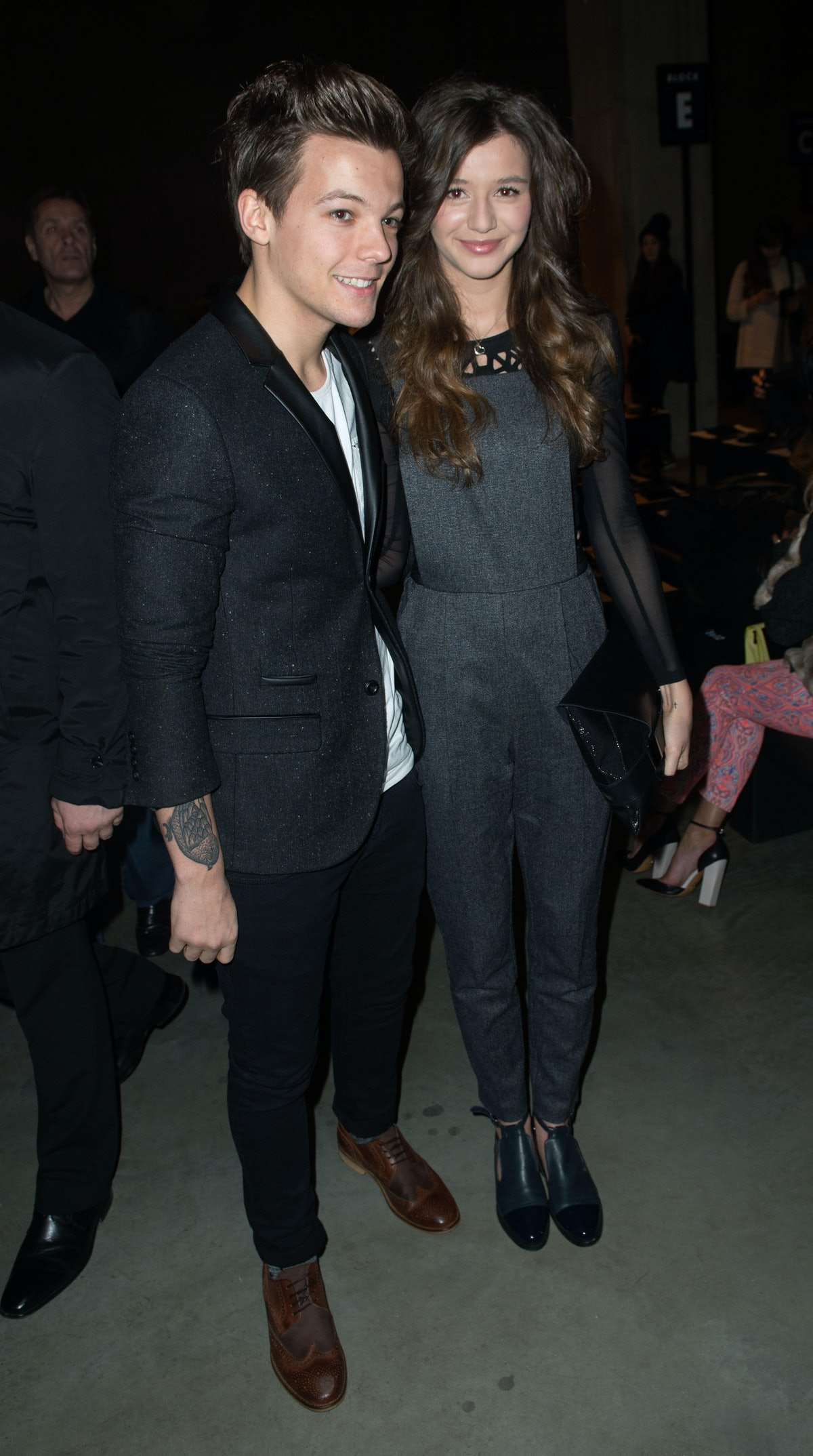 LONDON, ENGLAND - FEBRUARY 17:  Louis Tomlinson from One Direction and Eleanor Calder attend the Topshop Unique show at the Tate Modern during London Fashion Week Fall/Winter 2013/14 on February 17, 2013 in London, England. (Photo by Samir Hussein/Getty Images)