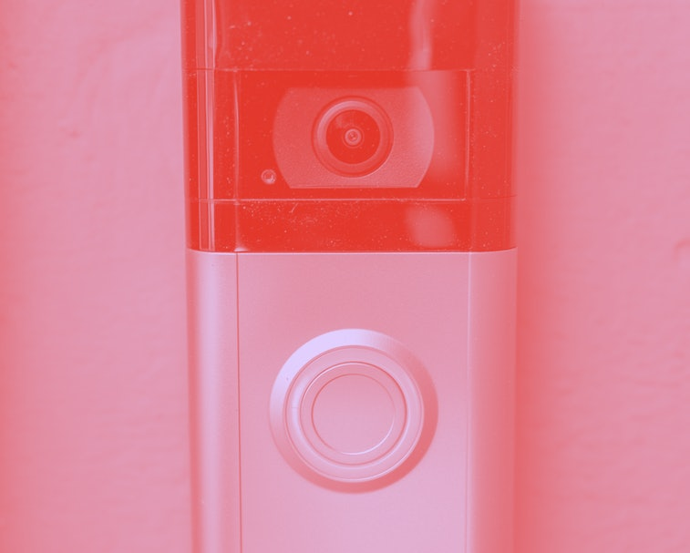 """Close-up of a video doorbell with a """"Ring"""" logo attached to a light-colored wall, February 17, 2021. (Photo by Smith Collection/Gado/Getty Images)"""