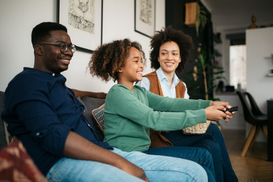Side view of an African American family relaxing at home, watching TV together and smiling