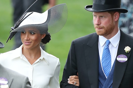 Britain's Prince Harry, Duke of Sussex (R) and his wife Britain's Meghan, Duchess of Sussex attend d...